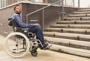 Man in a wheelchair at the bottom of a staircase unable to access entry to a building.