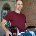 Man sitting in a wheelchair outside the front door of his home.