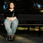 Girl who is blind, smiling and sitting on a bench