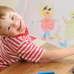 Boy with Downs Syndrome drawing with crayons