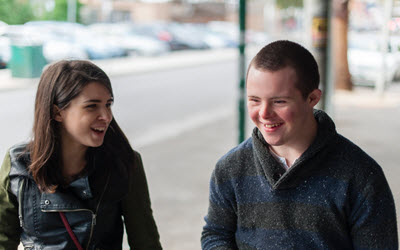 Boy with down syndrome and girl laughing and smiling