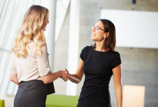 Two business women shaking hands in an office