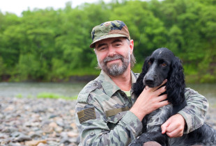 Veteran man near a river holding a dog