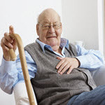Elderly man sitting in chair and holding his cane with his right hand.