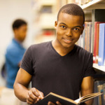 Male student in a library leaning against bookshelf.