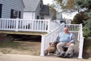 Man and dog in front of ramp leading to house