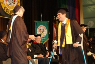 Man with crutches graduating and wearing cap and gown