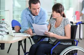Woman in wheelchair at work speaking with male co-worker