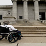 Woman in wheelchair in front of courthouse steps
