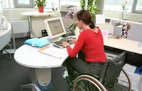 Woman in wheelchair working at desk using a computer