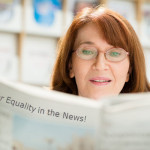 Woman reading newspaper with headline on back that says, Equip for Equality in the News!""