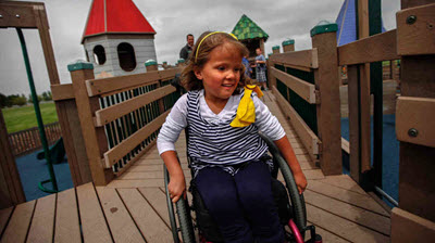 Girl in wheelchair on accessible playground.