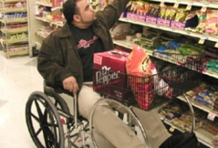 Man in wheelchair in grocery store reaching for items on a shelf
