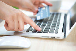 Close up of hands typing a credit card number into a laptop computer