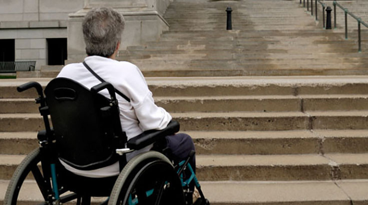 Woman in wheelchair in front of courthouse stairs