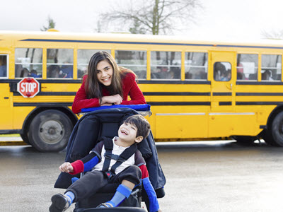 School standing behind brother in wheelchair, posing in front of yellow school bus.