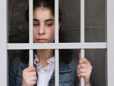 Teenage girl standing behind bars.