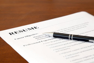Resume on a table with a pen on top.