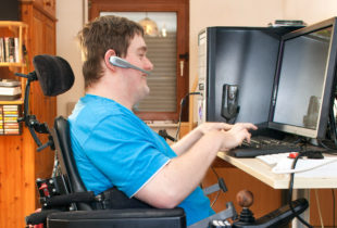 Man in a wheelchair typing on a computer and talking on a headset