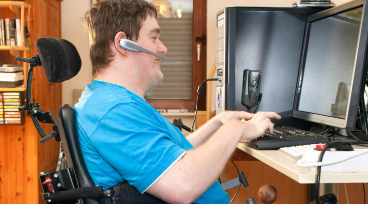 Man with spastic infantile cerebral palsy caused by a complicated birth sitting in a multifunctional wheelchair using a computer with a touch screen and wireless headset, side view.