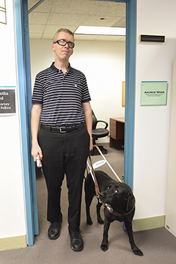 Andrew standing in his office doorway with a guide dog