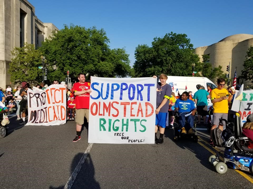 """Parade members in the street hold up posters that say """"Protect Medicaid"""" and """"Support Olmstead Rights."""""""